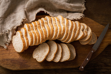 sliced bread on wooden board, top view