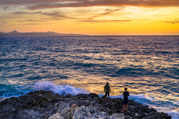 Wall Mural - Boys looking at Sunset over Mediterranean sea