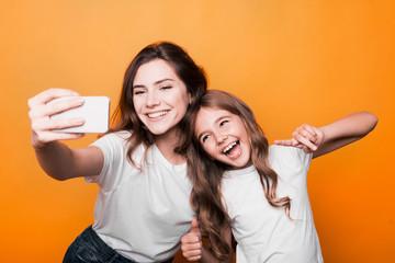 two sisters taking selfie in studio on orange background