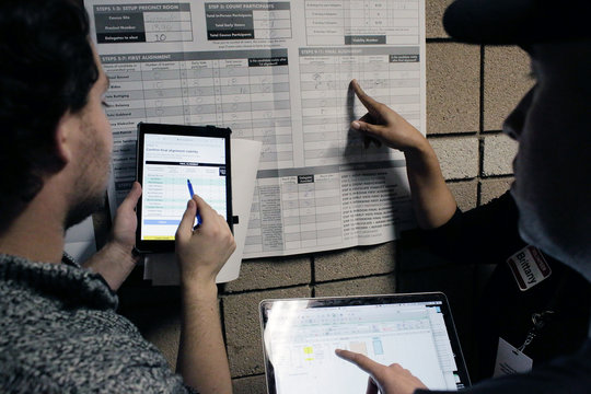 Volunteers use an iPad while a voter double checks caucus results using a spreadsheet on his laptop at a Nevada Caucus voting site at Coronado high school in Henderson