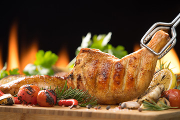 Wall Mural - Grilled chicken thigh with various vegetables on  chopping wood