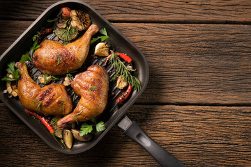 Fototapete - Top view of grilled chicken thigh with various vegetables on pan on old wooden background..