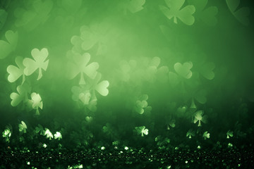 Green St Patricks day background with sparkling shamrock shapes