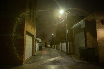 Wall Mural - Dark and eerie urban city alley at nightin the winter