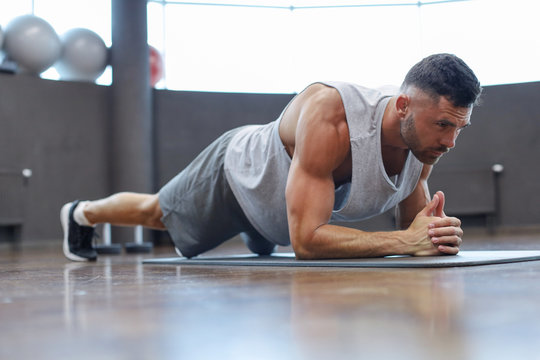 Portrait of a fitness man doing planking exercise in gym.