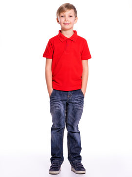 Young pretty boy posing at studio as a fashion model. Photo of a 8 years old kid. Full portrait of happy boy, isolated.  Portrait of white smiling kid in a red t-shirt and jeans. Boy in a full length