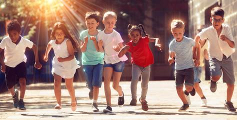 Group of joyful children running down the city street