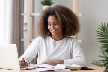 Happy african american teen high school student studying with laptop