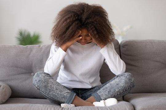 Depressed upset african american teen girl feeling hurt sitting alone
