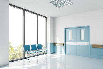 Blue chairs near window in empty hospital hall Fotomurales