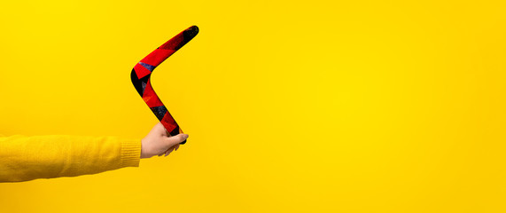 boomerang in female hand over yellow background, panoramic mock-up with space for text