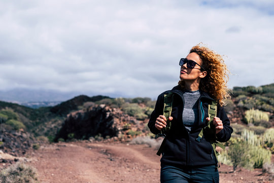 Happy independent beautiful adult caucasian woman in trekking outdoor leisure activity enjoying the nature - modern active people walking with backpack at the mountain