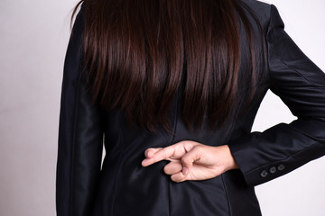Close up businesswoman with her fingers crossed behind her back - concept for good luck or dishonesty business.