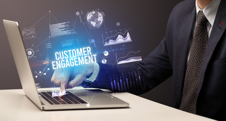 Businessman working on laptop with CUSTOMER ENGAGEMENT inscription, new business concept