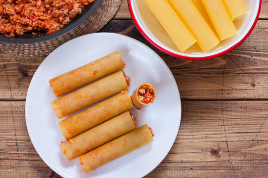 Step-by-step preparation of stuffed cannelloni with bechamel sauce, step 5 - stuffing with sauce of bolognese raw cannelloni sauce, top view, horizontal