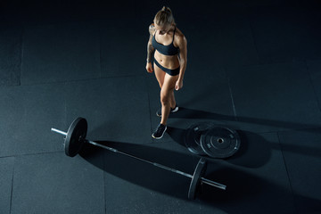 Girl with a barbell in the gym. A young slender Caucasian woman comes up to the bar to start exercising. Top view. Barbell and athlete on a black background.