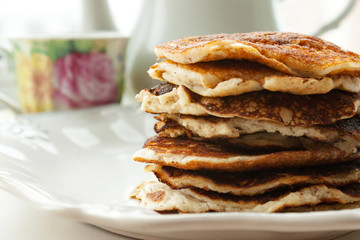 Low Carb Keto Diet Pancakes from almond coconut flour stack on white plate and cup of cocoa on wooden table background close up view. Selective focus. Copy space. Ketogenic concept