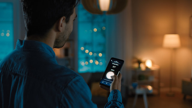 Young Handsome Man is Holding Smartphone with Active Smart Home Application. Person is Tapping the Screen to Turn On/Off the Lights in the Room. It's Cozy Evening in the Apartment.