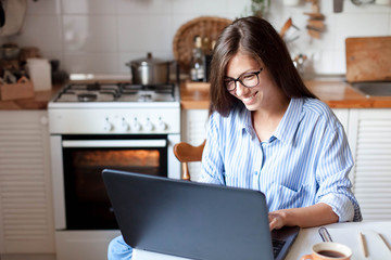 Young woman working from home office. Freelancer using laptop and the Internet for shopping online. Happy girl smiling. Workplace in cozy kitchen. Successful female business. Lifestyle moment.