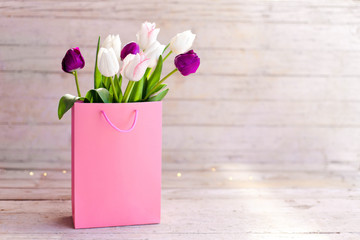 Spring flowers. Blooming tulips in pink shopping bag at wooden background. White, lilac and purple...