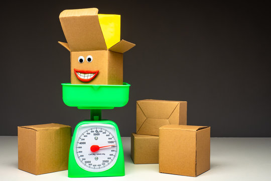 Cardboard boxes and scales. Weighing parcels before sending. Work of the postal service. Determining the cost of delivery of parcels. Courier delivery.