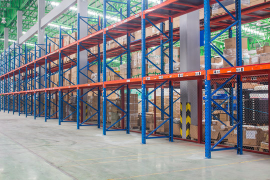 The empty rows of shelves with boxes in warehouse.