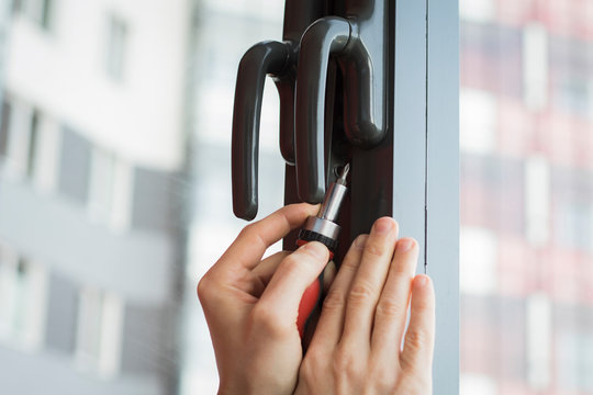 Handyman installing and repair the a lock in front the plastic door and plastic window.
