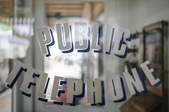 Shallow focus of Public Telephone decals seen on the door of a vintage phone booth. The old style phone can be seen through the glass.