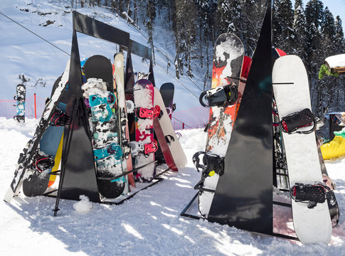 Alpine skis and snowboards equipment leaning on ski rack in winter ski resort
