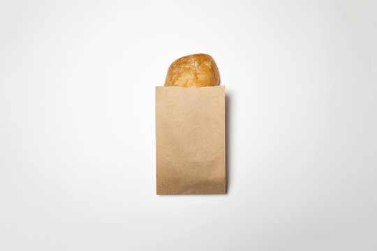 Fresh Bread in a brown kraft Paper Bag Mockup on white background.High resolution photo.