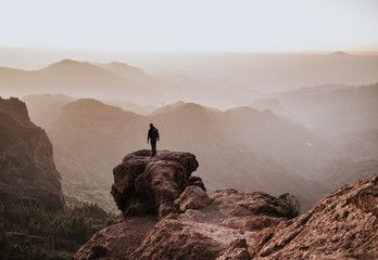 Behind shot of a man with a backpack standing on top of a cliff and enjoying the view