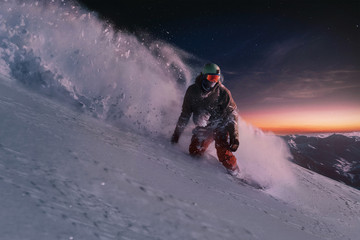 night skating snowboarder curved and brakes spraying loose deep snow on freeride slope under the starry sky and sunset light