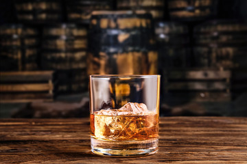 Glass of whiskey with ice with barrels on background Fototapete