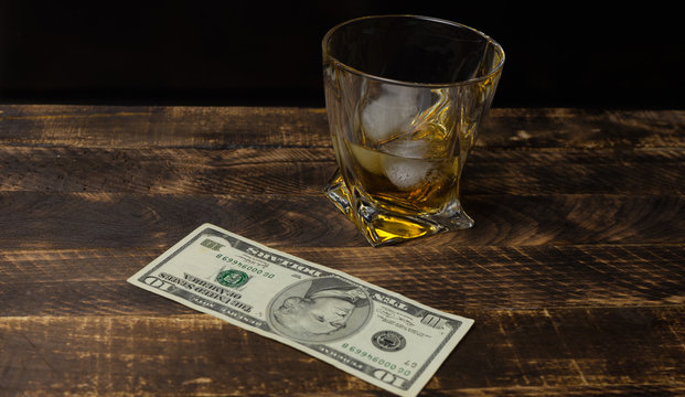 Glass of whiskey with money on a wood table.
