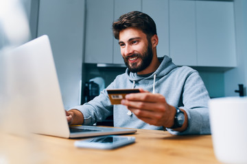 Cheerful young man paying bills online with credit card and laptop