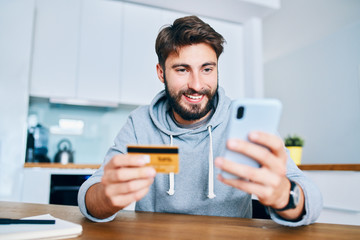 Young man sitting at home paying for food online with smartphone and credit card