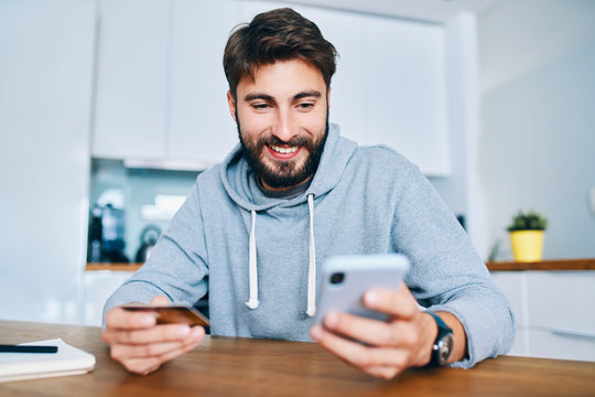 Smiling young man sitting at home and paying online with credit card and smartphone