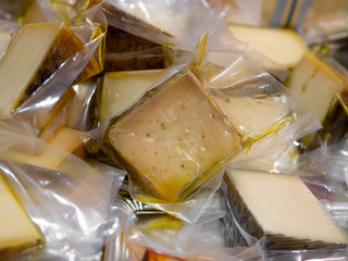 Various pieces of cheese in olive oil in plastic bags at a market stand