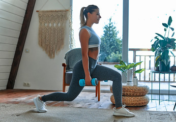 Woman doing exercises at home. Wall mural