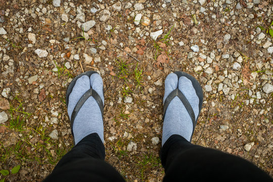 Fashion police victim - wearing sandals over feet covered with gray socks. Terrible thing to do.