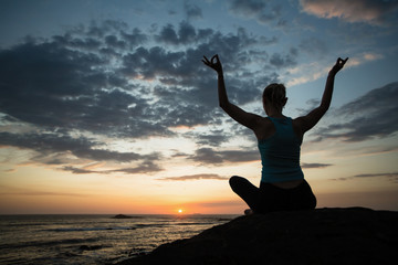 Yoga woman in lotus meditating on the ocean coast at dusk.