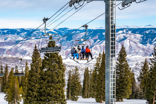 Skiers and snowboarders ascend the Alpine Springs chairlift at the Aspen Snowmass ski resort, in the Rocky Mountains of Colorado on a partly cloudy winter day.