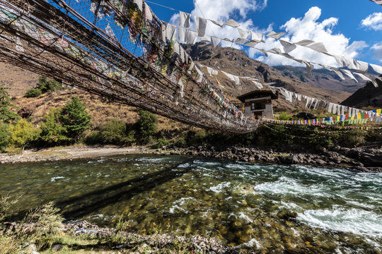 The Mountain landscape of Bhutan, the Paro Chu River beside the Paro - Thimphu Highway. A walking suspension bridge over a mountain river with colorful prayer flags in the Bhutanese Mountains.