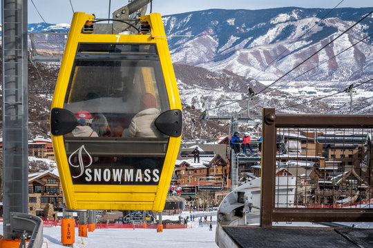 """Snowmass Village, Colorado - January 8, 2020: A gondola known as the """"Skittles"""" people mover transports people from the Base Village to the Snowmass Mall, with Rocky Mountains in the background."""