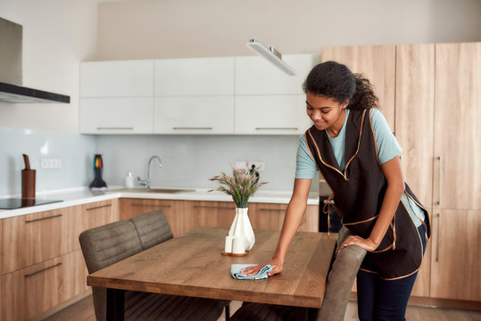 Pure clean. Young positive afro american house maid in apron cleaning table in the modern kitchen. Professional female cleaner at work