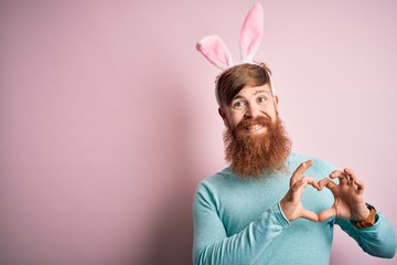 Hipster Irish man with beard wearing easter rabbit ears over isolated pink background smiling in love showing heart symbol and shape with hands. Romantic concept.