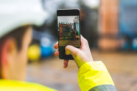 Architect holding a smartphone on construction site - young construction worker is using mobile phone on site - Construction worker with building plans and cellphone - Focus on mobile. warm filter