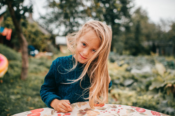 Portrait of young lovely girl lies on the coverlet in the garden and smile