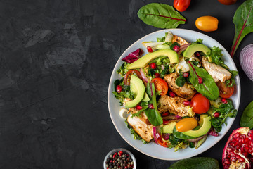 Grilled chicken breast and avocado salad with mixed greens, tomatoes and pomegranate in a plate on dark background