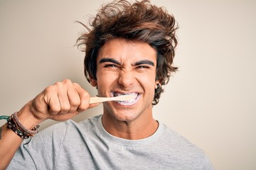 Young handsome man smiling happy. Standing with smile on face whasing tooth using toothbrush over isolated white background Papier Peint